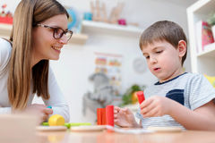 Kindergarten Teacher Supports Cute Boy in Educational Game Play. Early education Stock Photos