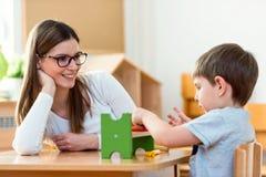 Kindergarten Teacher Supports Cute Boy in Educational Game Play. Kindergarten Teacher Supports Cute Kid in Educational Game Play. Early education Royalty Free Stock Image