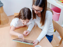 Kindergarten Teacher Supports Cute Girl in Educational Game Play on digital tablet. Kindergarten Teacher Supports Cute Kid in Educational Game Play. Early Royalty Free Stock Photography