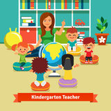 Kindergarten teacher teaching kids geography  Royalty Free Stock Photos