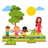 Kindergarten teacher walking with kids outdoors Stock Photos