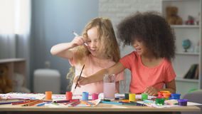 At kindergarten, two positive multiracial girls painting with watercolors, hobby. Stock footage stock footage