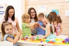 Kindergartener with kids group in classroom stock images