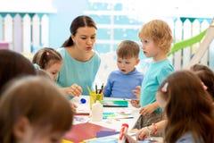 Kindergartener teaches kids handcraft at nursery or playschool stock photography