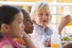 Kindergartenkinder, die das Mittagessen essen lizenzfreies stockfoto