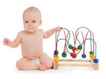 Kindergartenkinderbabykleinkind, das hölzernes educa sitzt und spielt stockbilder