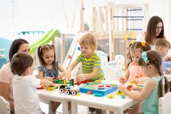 Kindergartenkinderspielspielwaren mit Lehrer im Spielzimmer an der Vorschule getrennte alte Bücher lizenzfreie stockfotos