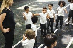 Kindergartenstudenten, die zusammen in einer Linie stehen Stockfotografie
