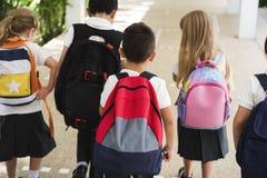 Kindergartenstudenten, die zusammen nach Klasse stehen lizenzfreie stockfotografie