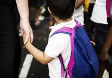 Kindergartenstudentenhändchenhalten mit Erwachsenem lizenzfreies stockbild