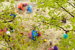 Kindergartner under trees. Kids playing on sand playground under tree crowns Stock Image