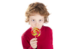 Kindergekreuzte Augen, die Lutschersüßigkeit lecken Lizenzfreie Stockbilder