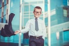 Kindergeschäftsmann bewegt seine Jacke wellenartig Stockbild
