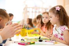 Kindergruppe, die Künste und Handwerk in der Kindertagesstättenmitte lernt stockbild