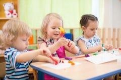 Kindergruppe, die Künste und Handwerk im Kindergarten mit Interesse macht Lizenzfreie Stockfotografie