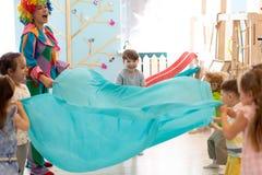Kindergruppe haben Spaß auf Partei Clown unterhält Kinder lizenzfreie stockfotos