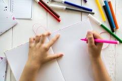 Kinderhände auf einem leeren Blatt des Notizbuches Lizenzfreie Stockbilder