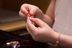 Kinderhände aufgereihte Perlen auf Thread Stockfotos