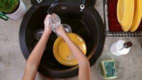 Kinderhände, die ein Trinkglas waschen stock video