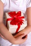 Kinderhände, die eine Geschenkbox halten Lizenzfreie Stockfotos