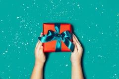 Kinderhände, die schöne Geschenkbox auf blauem Hintergrund halten lizenzfreie stockfotos