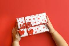 Kinderhände, die schöne Geschenkbox auf rotem Hintergrund halten Feiertags-, helle und festlicheansicht, flache Lage stockfoto