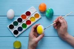 Kinderhände malen Osterei durch gelbe Farbfarbe und Farben, Malerpinsel, gemalte Ostereier Stockfotos