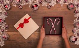Kinderhände mit der Weihnachtsgeschenkbox, die Zuckerstangen enthält stockbild