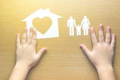 Kinderhände mit kleinem Modell des Hauses und der Familie lizenzfreies stockbild