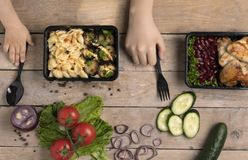 Kinderhände mit schwarzem Löffel und Gabel unter Nahrungsmittelbehälter mit gegrillten Hühnerflügeln, blaues Tuch lizenzfreies stockfoto