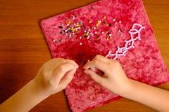 Kinderhände sammeln rosa Perlen auf einer Zugschnur Stockfoto