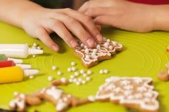Kinderhände verzieren Weihnachtsplätzchen - Nahaufnahme Lizenzfreies Stockfoto