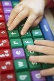 Kinderhand, die auf bunter Computer-Tastatur schreibt Lizenzfreie Stockbilder