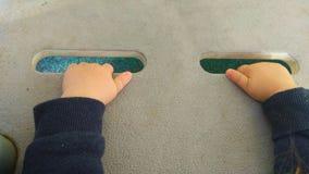 Kinderhand, die graue Ergreifungsplatte hält stockfotos