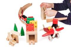 Kinderhand, die hölzerne Spielwaren spielt Stockbilder