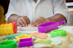 Kinderhand, die mit Lehm spielt Stockbilder