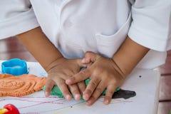 Kinderhand, die mit Lehm spielt Lizenzfreie Stockfotografie