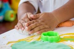Kinderhand, die mit Lehm spielt Stockfoto