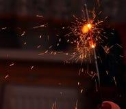 Kinderhand, eine brennende Wunderkerze halten Lizenzfreie Stockbilder