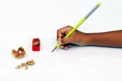 Kinderhand mit Bleistift und Bleistiftspitzer Stockfotografie