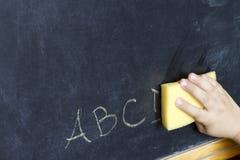 Kinderhand säubert Buchstabe-ABC-Bildungshintergrund Stockfoto