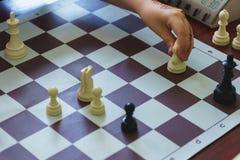 Kinderhand trifft eine Maßnahme auf dem Schachbrett Lizenzfreies Stockfoto