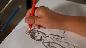 Kinderhand zeichnet ein rotes Kreuz auf dem Hut des Doktors auf Papier Nahaufnahme stock video footage