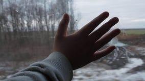 Kinderhandim zug Fenster auf dem Hintergrund der Landschaft, Schnee bedeckte Feld und Bäume stock footage