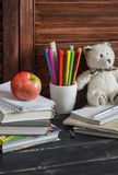 Kinderinländischer Arbeitsplatz und Zubehör für Aus- und Weiterbildung - Bücher, Zeitschriften, Notizblöcke, Notizbücher, Stifte, Lizenzfreies Stockfoto