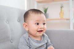 Kinderjaren, kleutertijd en gelukkige mensenconcept - weinig zitting van het babymeisje op bank thuis stock fotografie