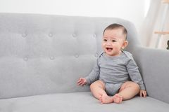 Kinderjaren, kleutertijd en gelukkige mensenconcept - weinig zitting van het babymeisje op bank thuis stock foto