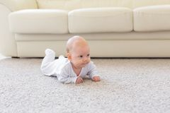Kinderjaren, kleutertijd en mensenconcept - weinig babyjongen of meisje die op vloer thuis kruipen stock fotografie