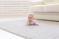 Kinderjaren, kleutertijd en mensenconcept - weinig babyjongen of meisje die op vloer thuis kruipen royalty-vrije stock fotografie