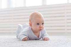 Kinderjaren, kleutertijd en mensenconcept - weinig babyjongen of meisje die op vloer thuis kruipen stock foto